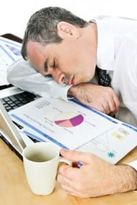 Businessman asleep at his desk on top of piles of sleep references