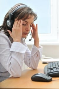 Tired woman in pain sitting at her computer - suffering from sleep problem and myalgia?.