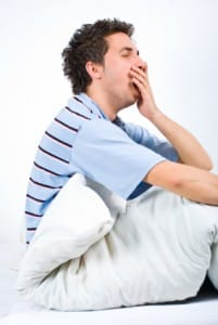 Yawning young man on bed in need of sleep therapy treatment