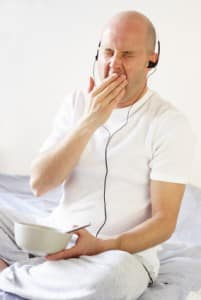 Yawning man with headphones on having breakfast in bed - he needs sleep therapy