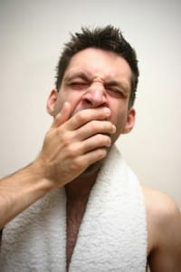 Yawning man with towel around his neck - he could do with Relax-the-Mind sleep therapy!