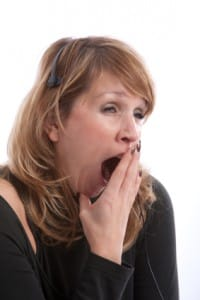 Woman yawning very wide - perhaps she is suffering from a sleep disorder?