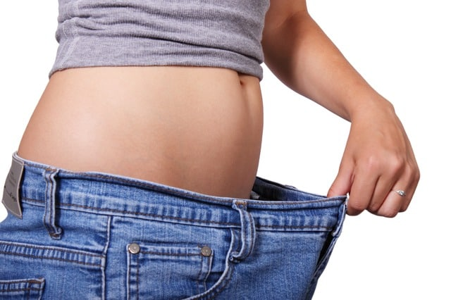 Woman's flat belly in too large jeans - she no longer needs to lose weight!